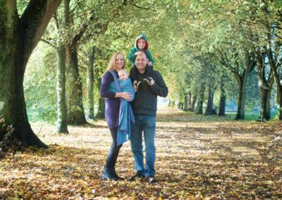 family smiling in the autumn leaves in farnham park