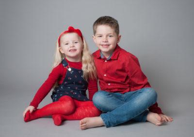siblings in red smiling in Runfold