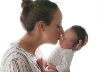 mummy kissing newborn baby