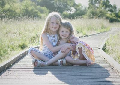 sisters cuddling on a boardwalk in farnham photoshoot