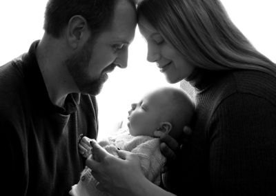mummy and daddy with their baby in a photo shoot in farnham