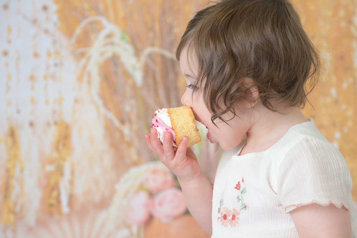 one year old eating cake at her cake smash session
